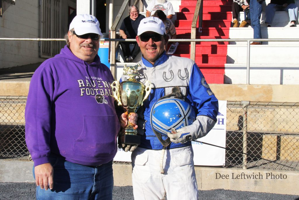 Leading driver Tyler Shehan accepts a trophy from Racing Secretary Mike Wandishin. Photo by Dee Leftwich.